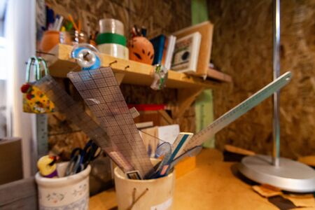 A close-up view of plastic grid rulers in a stationery pot underneath a bookshelf with sketchbooks inside a vintage atelier. Tools of a creative designer.