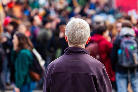 An older man is viewed from the rear with grey hair, contemplating a crowd of environmentalists marching in the city, people seen blurry in the background Stok Fotoğraf