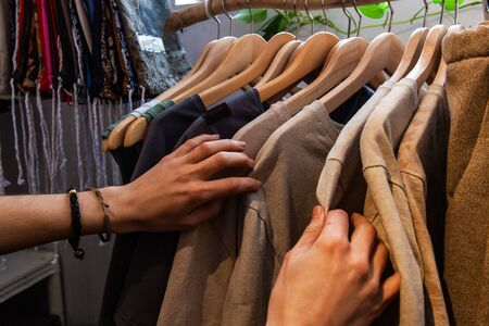 Hands of a trendy girl are viewed closeup, browsing clothing racks inside an eco-friendly fashion store. Authentic clothes hang from a rustic rail.