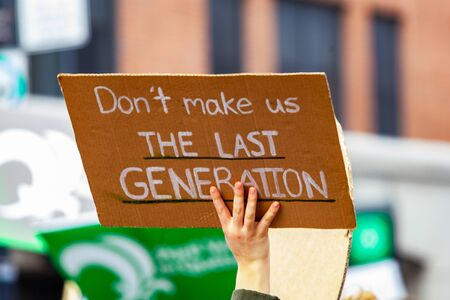 A cardboard sign is seen closeup in the hand of an environmental campaigner, saying dont make us the last generation, during a rally on an urban city street. Stok Fotoğraf