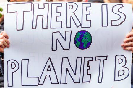 Een zelfgemaakte plakkaat wordt van dichtbij bekeken en leest dat er geen planeet B is, terwijl milieuactivisten een stadsdemonstratie organiseren tegen de opwarming van de aarde
