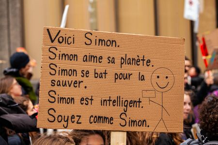 A French cardboard sign depicts the this is Simon, be like Simon meme as he fights to save planet earth, viewed close up during a protest against climate change