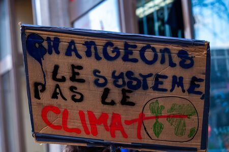 A close up view of a homemade French placard saying change the system, not the climate as ecological activists march for change on an urban city street. Imagens
