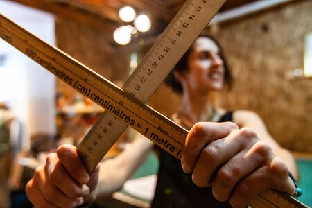 A female fashion worker stands inside an atelier, she holds two metric rulers, used to measure fabrics and sketch new designs.