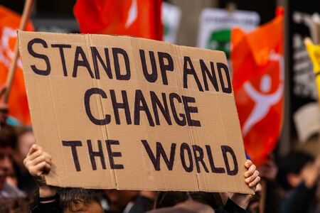 A cardboard sign is seen close up, saying stand up and change the world, as eco-activists march for the environment on a street in Montreal, Canada