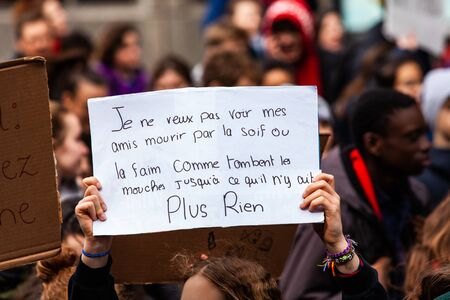 A French placard is viewed close-up, saying I do not want to see my friends die by thirst or hunger, among a crowd of eco-activists in the city Stok Fotoğraf