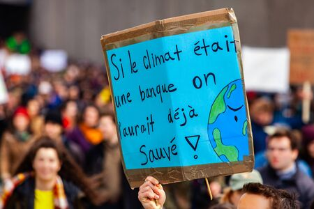 A homemade French sign is viewed closeup, saying if the climate was a bank it would have already been saved, as ecological activists march for the environment.