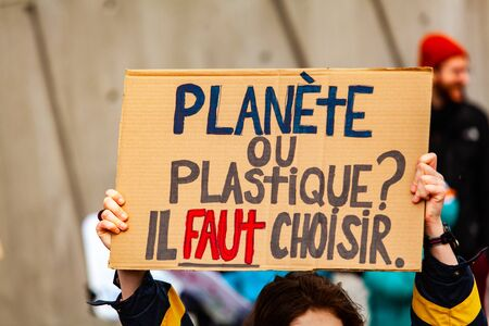 A close up view of a French sign, saying plastic or planet, you have to choose as environmental protestors march on a street in Montreal, Canada.