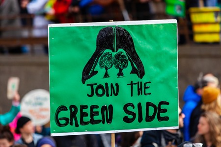 A close up view of a homemade sign during a street rally for the environment, depicting darth vader and saying join the green side. Redakční