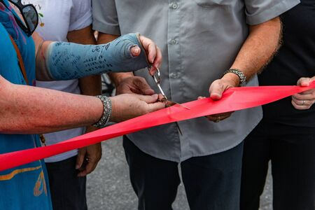Atmosphere at outdoor farmer's market. A symbolic moment is captures closeup, during the grand opening of a local community fair, as local person wearing an arm cask uses scissors to cut a red ribbon Banco de Imagens - 131713757
