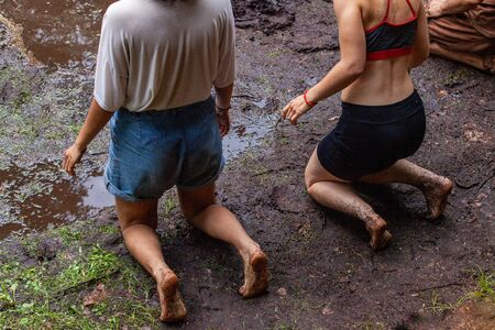 Diverse people enjoy spiritual gathering Two young caucasian woman are seen kneeling in mud, wearing shorts with sludge covered bare legs as they practice meditation during a forest retreat.