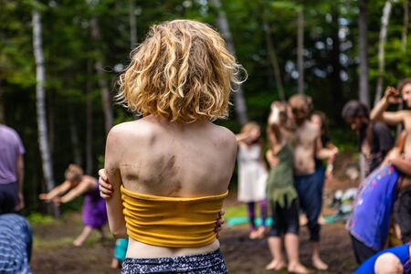 Diverse people enjoy spiritual gathering A young caucasian woman is seen from behind wearing a yellow crop top with mud stained skin and unkempt hair as people practice playful dance in nature.