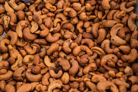Organic produce at a farmers market. A closeup view of roasted cashew nuts, filling the frame, healthy and nutritious snacks sold on a market stall during a local food fair.