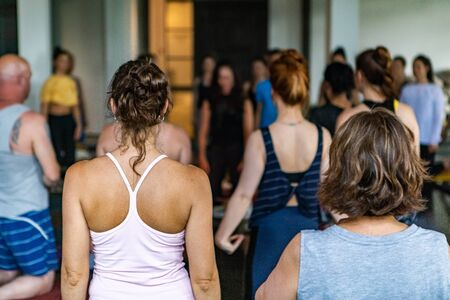Diverse group of people in yoga class. Spiritual people of all ages and backgrounds are seen kneeling inside a yoga club as they partake in 108 salutations to the sun. Traditional Hindu practice.