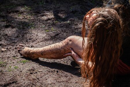 Diverse people enjoy spiritual gathering A young caucasian girl is seen closeup, sitting in mud with a dirty bare leg. Practicing mindful stretches with room for copy. Stok Fotoğraf