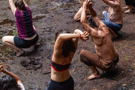 Diverse people enjoy spiritual gathering An intergenerational group of people are seen praying with hands clasped together above heads and crouching barefooted in mud, close to earth and nature.