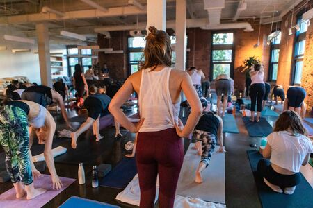 Diverse group of people in yoga class. An exhausted caucasian woman is seen from the rear, standing with hands on hips as she takes a break from a taxing workshop of 108 salutations to the sun.