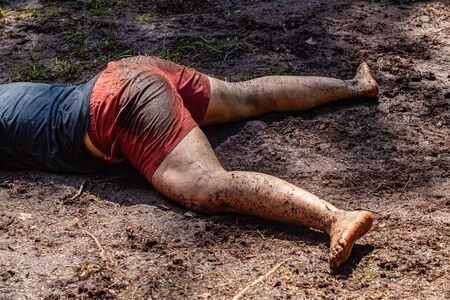 Diverse people enjoy spiritual gathering A close up view on the legs of a young caucasian woman, wearing short shorts and practicing yoga in a muddy woodland clearing during a mindful retreat.