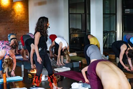 Diverse group of people in yoga class. A motivational yogic trainer is seen encouraging participants during a workshop dedicated to 108 rounds of sun salutations. Downward facing dog pose is seen. 스톡 콘텐츠