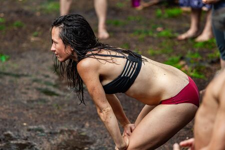 Diverse people enjoy spiritual gathering A young caucasian woman wearing underwear is seen from the side, standing in mud as people experience multicultural rituals in nature. Stok Fotoğraf