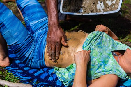 Diverse people enjoy spiritual gathering A closeup view of a young woman lying on her back in a campsite as another person places mud on her skin during an alternative healing ceremony.