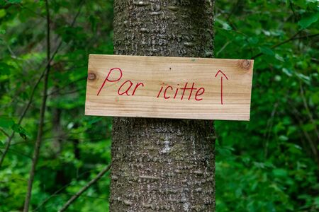 Diverse people enjoy spiritual gathering A small French sign, saying around here, is seen with a red arrow pointing towards a woodland trail near a campsite.