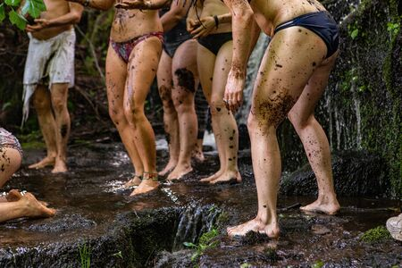 Diverse people enjoy spiritual gathering A multigenerational group of people are seen having a traditional mud bath in a rock pool during a mystical retreat celebrating mother nature.