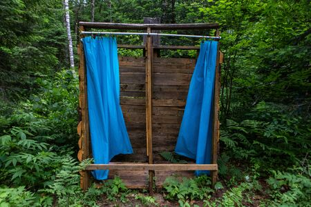 Diverse people enjoy spiritual gathering Basic wash and hygiene facilities are viewed in dense woodland, at a campsite celebrating native cultures. Ramshackle timber construction in forest.