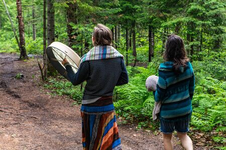 Diverse people enjoy spiritual gathering A young shaman couple in colorful clothes are seen walking in a dense forest, carrying a traditional native drum during an event celebrating cultures. Archivio Fotografico - 131715117