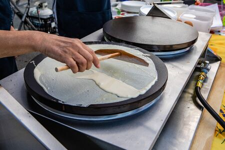 Fresh food at outdoor farmer's market. A cook is seen up close using a wooden utensil to spread fresh crepe mix over a hotplate on a food stand during a local fair for farmers and cottage industries.