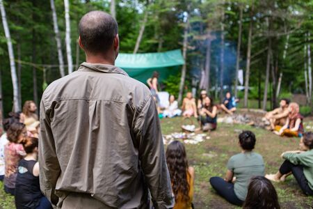 Diverse people enjoy spiritual gathering A middle aged guy with a bald spot is viewed from behind, standing amongst a group of intergenerational people enjoying mystical rituals at a woodland retreat Stock Photo