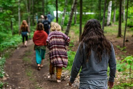 Diverse people enjoy spiritual gathering A group of mixed people from all backgrounds are seen following a wooded trail as they seek mindful contemplation and spiritual guidance.