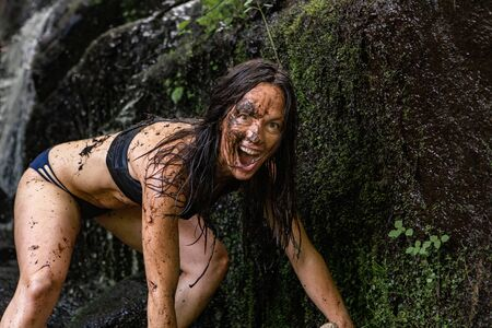 Diverse people enjoy spiritual gathering A young and playful shamanic woman is seen closeup by a river, in lingerie with mud covered face and body, playfulness and freedom during nature retreat.