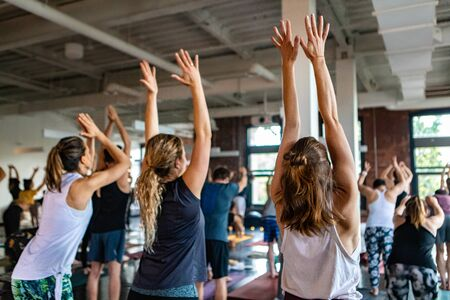Diverse group of people in yoga class. People inside a gymnasium are seen from behind with raised hands as they practice 108 salutations to the sun. A divine set of exercises carried out during solstice.