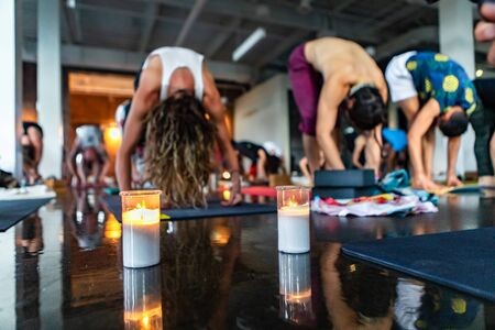 Diverse group of people in yoga class. A mixed class of people are seen practicing a spiritual set of exercises inside a large hall. Candles set the atmosphere during 108 sun salutes. Archivio Fotografico