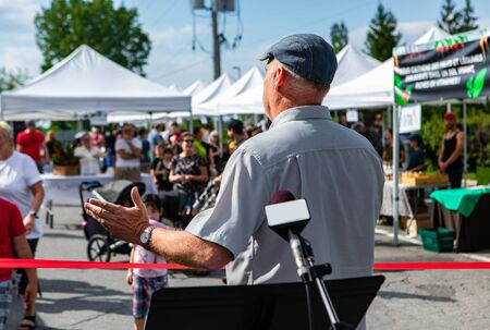 Atmosphere at outdoor farmer's market. An older man wearing a cap is seen from the back during the opening of a local farming and agricultural fair. Blurry stalls and people are seen in background. Stock fotó