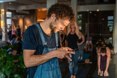 Diverse group of people in yoga class. A close up view of a thirty something Caucasian guy absorbed in his mobile phone. Light from the screen illuminates face as he uses device during gym session. Banco de Imagens - 131715528