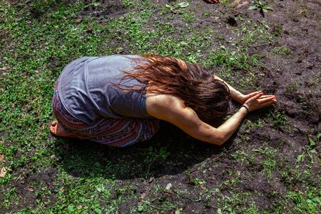 Diverse people enjoy spiritual gathering A high angle view of a young Caucasian woman practicing yoga in a muddy forest clearing, seen in balasana (child's resting pose), with face to ground.