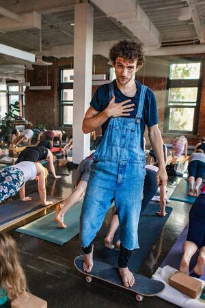 Diverse group of people in yoga class. A thirty year old Caucasian male wearing denim dungarees is seen balancing on a skateboard as people pose on exercise mats during a yogic workshop.