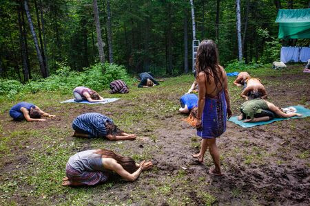 Diverse people enjoy spiritual gathering A mystical cultural guide wearing traditional native dress is seen walking among people praying close to earth, sitting bent forward with head to ground.
