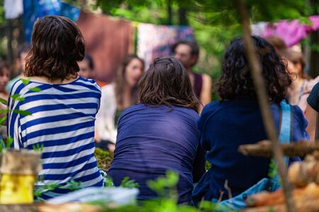 Diverse people enjoy spiritual gathering A large mixture of multicultural people are seen sitting in a circle in a forest campsite during a retreat for mindfulness and contemplation.