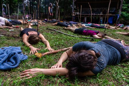 Diverse people enjoy spiritual gathering A multigenerational group of people are seen meditating in the forest, lying on the ground at a native cultures retreat with room for copy. Archivio Fotografico - 131715753