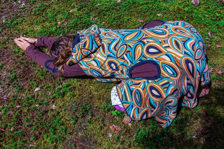 Diverse people enjoy spiritual gathering A young woman is seen practicing alternative healing during a woodland retreat celebrating native and shamanic cultures, wearing a colorful and bold jacket.