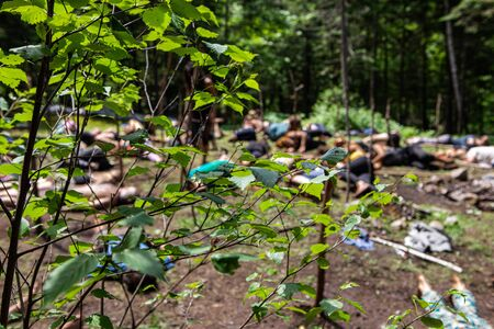 Diverse people enjoy spiritual gathering Blurry people are seen meditating behind tree branches during a natural retreat celebrating native exercises and cultures.