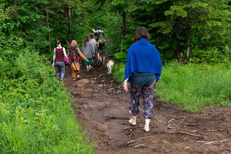 Diverse people enjoy spiritual gathering A woman is seen walking barefoot on a woodland trail with people of all ages during an event celebrating traditional shaman and native cultures.