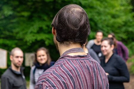 Diverse people enjoy spiritual gathering A person wearing a hairnet and striped shirt is seen standing in a woodland retreat, food server as people gather for mindful weekend. Archivio Fotografico