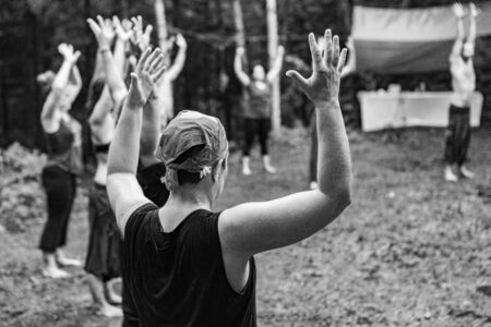 Diverse people enjoy spiritual gathering A black and white view on a diverse group of people experiencing shamanic based meditation during a mindfulness retreat in the forest, with copy-space.