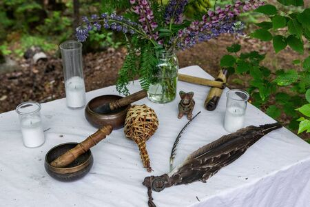 Diverse people enjoy spiritual gathering Sacred objects, including candles and eagle feather, are seen closeup on a table in a campsite during a shamanic and mystical retreat.