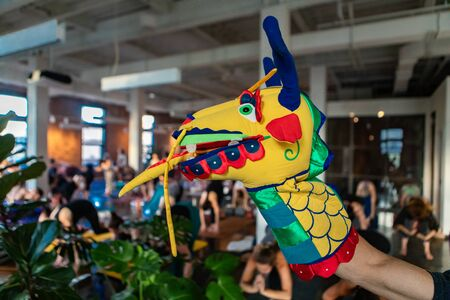 Diverse group of people in yoga class. A close up and side profile view of a hand puppet on the arm of a person, a colorful and fun dragon's head used to motivate people during grueling gym workout.