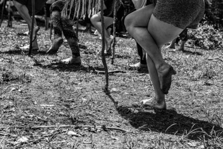 Diverse people enjoy spiritual gathering A closeup view on the legs of a group of people in standing yogic poses outdoors in nature, using sticks and bare feet close to earth. Archivio Fotografico